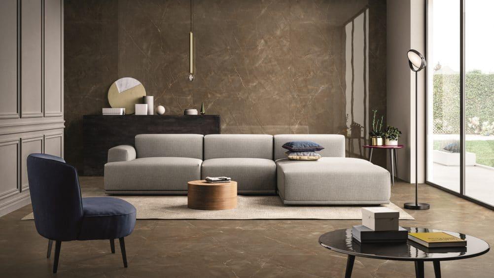 Sala de estar ampla com paredes de vidro do lado direito. No fundo temos um sofá grande e uma mesa, mais à frente temos uma poltrona azul e mesinhas.  O revestimento utilizado foi porcelanatos gigantes que imita mármore, instalados no piso e parede do fundo.