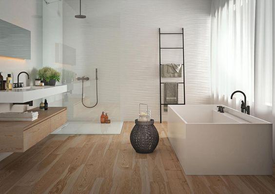 banheiro amplo com box ao fundo, lavabo branco do lado esquerdo e banheira branca retangular do lado direito. Nas paredes e no chão da ducha há porcelanatos brancos, e no piso, porcelanato que imita madeira.