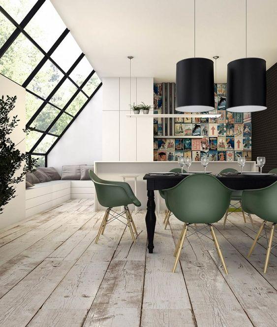 Cozinha com vista para área externa, com: balcão branco ao fundo, mesa preta e cadeiras verdes à frente. No piso foi utilizado porcelanato que imita madeira.
