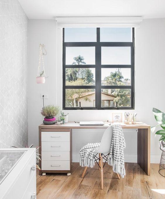 Home Office com paredes brancas, escrivaninha marrom e uma grande janela à frente da escrivaninha. No piso foi utilizado porcelanato que imita madeira.