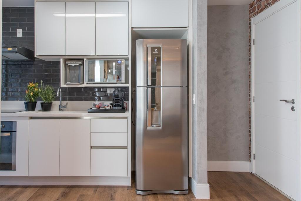 Cozinha combina piso de madeira com elementos industriais como a parede de cimento queimado, tijolinho e revestimento de metrô.