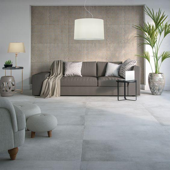 32 ideias inspiradoras para usar porcelanatos na sala Sala de estar com porcelanato que imita concreto bruto. É uma sala ampla com um sofá na parede do fundo, esta mesma parede tem porcelanato quadriculado no centro e porcelanato branco nas laterais.