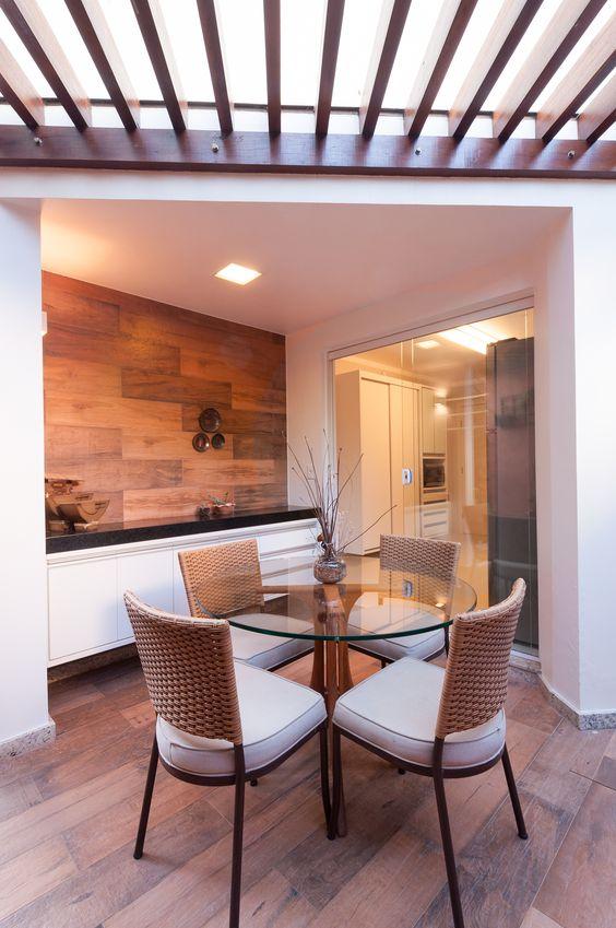 Nesta área externa foi utilizado porcelanato que imita madeira na parede do fundo e no piso. Nesta imagem, ainda existe um balcão ao fundo e uma mesa redonda de vidro com cadeiras brancas, ao centro.