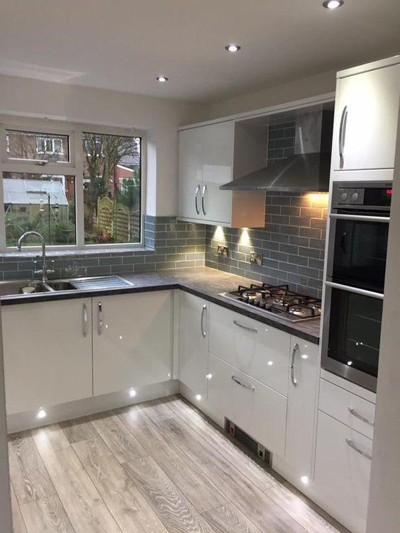 cozinha com azulejos subway, armário branco e porcelanato que imita madeira acinzentada.