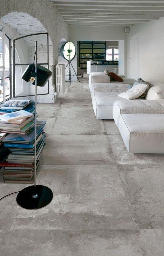 32 ideias inspiradoras para usar porcelanatos na sala Sala de estar ampla e minimalista de apartamento. Nesta sala de estar, temos sofás brancos do lado direito e grandes janelas do lado esquerdo. A parede das janelas é revestida com tijolinhos naturais brancos, e o piso é porcelanato que imita concreto.