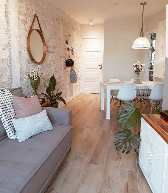 apartamento com sala de estar e jantar integradas. Parede com temática escandinava, porcelanato que imita madeira e mesa e cadeiras brancas.