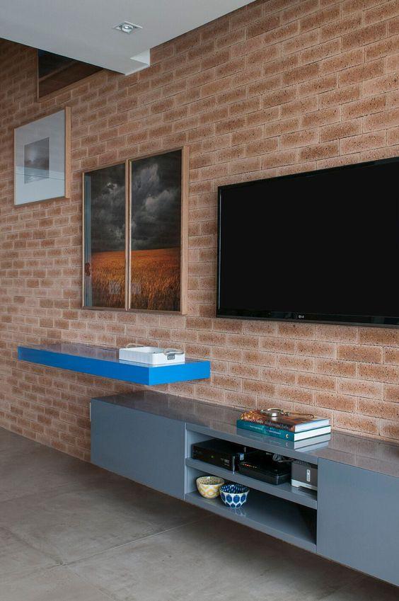 32 ideias inspiradoras para usar porcelanatos na sala Sala de estar com revestimento de tijolinhos na parede e porcelanato que imita cimento queimado no piso. Nesta sala de estar, temos: tv, bancada, raqui e quadros, todos instalados na parede de tijolinhos.