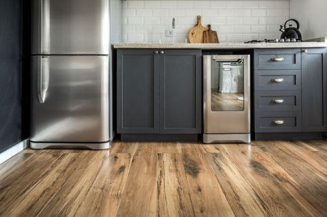 cozinha no estilo escandinavo com armários e eletrodomésticos com cores neutras, azulejo subway branco e porcelanato que imita madeira.