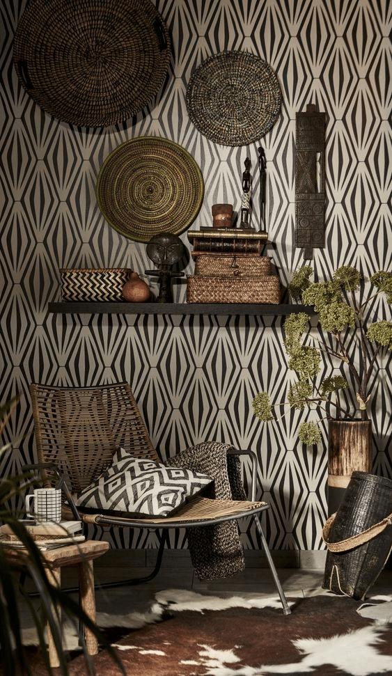 Estilo boho. Papel de parede preto e branco com figuras geométricas, cachepôs com plantas, cadeira de descanso, almofada com estampa étnica e souvenirs.