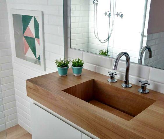 banheiro com azulejo subway branco e lavabo branco com bancada de porcelanato que imita madeira.