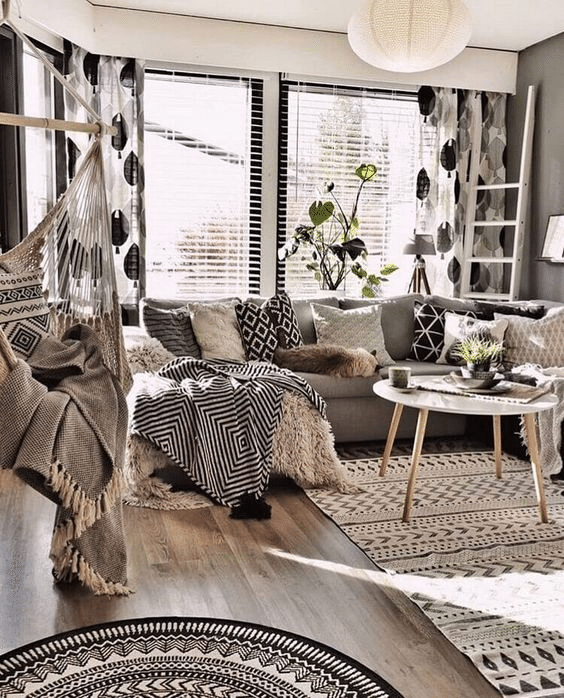 Sala de estar em estilo bohemian. Tapetes com estampas étnicas, diversos tecidos cashmeres, almofadas em estampas étnicas e adamascadas .