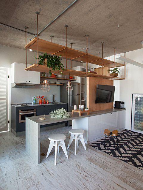 Cozinha e sala dividas por um balcão grande. Cimento Queimado no teto Decoração no estilo industrial, com pia cinza, armários brancos e porcelanato que imita madeira acinzentada.