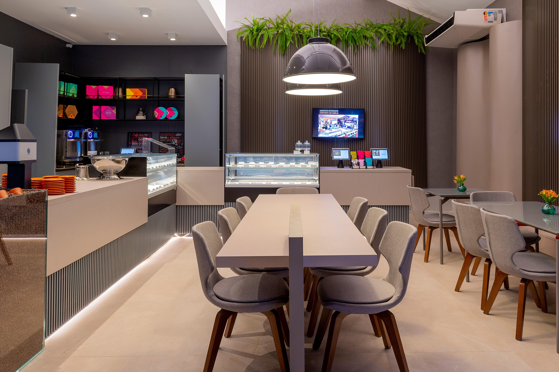 Jóia Bergamo na CASACOR 2019. Café com sofisticadas mesas de madeiras e revestimento de porcelanato com efeito madeira.