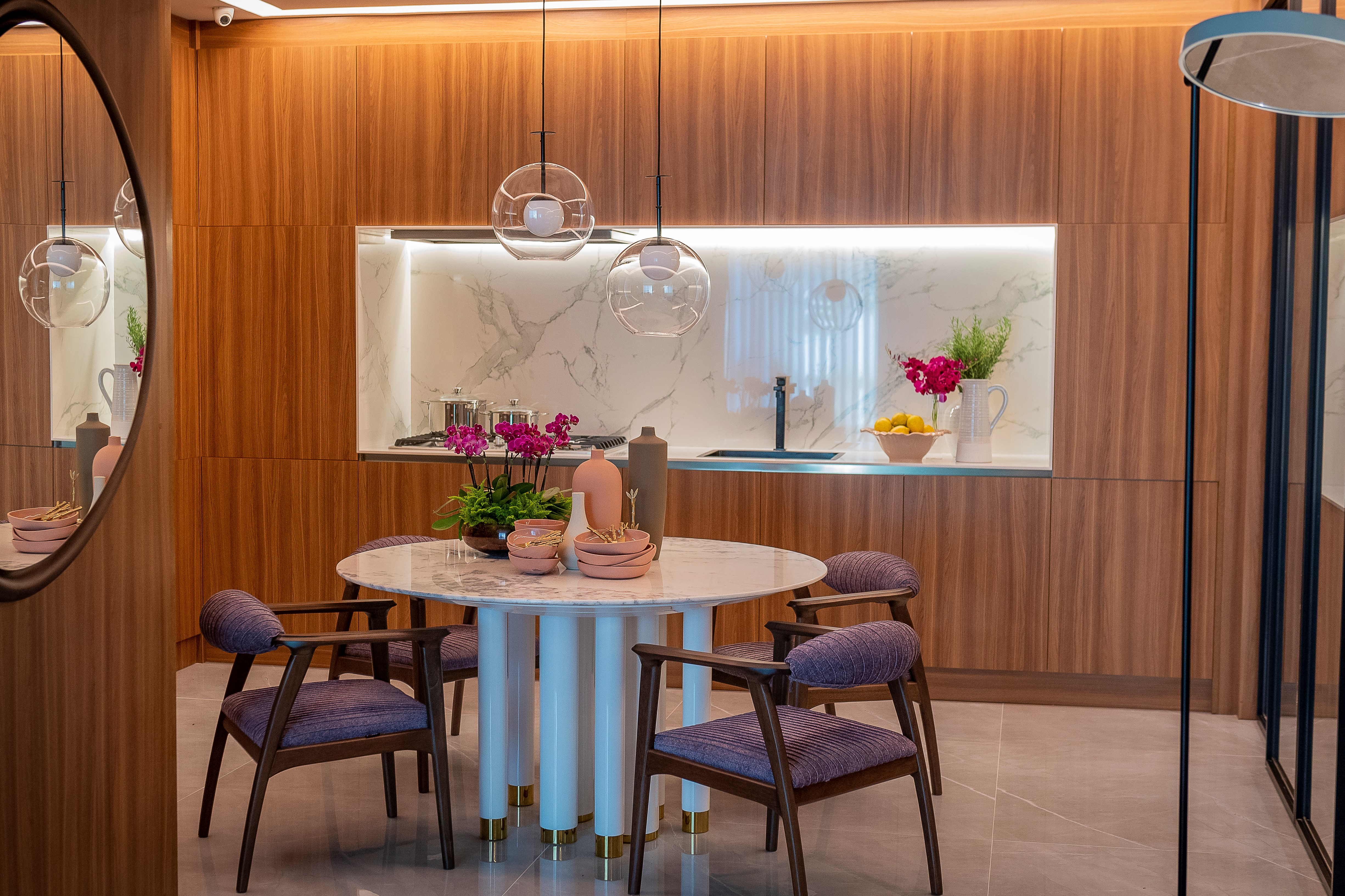 Patrícia Hagobian no CASACOR 2019. Living com revestimento de porcelanato com efeito madeira nas paredes, e porcelanato com efeito cimento neutro. Mesa e cadeiras elegantes.