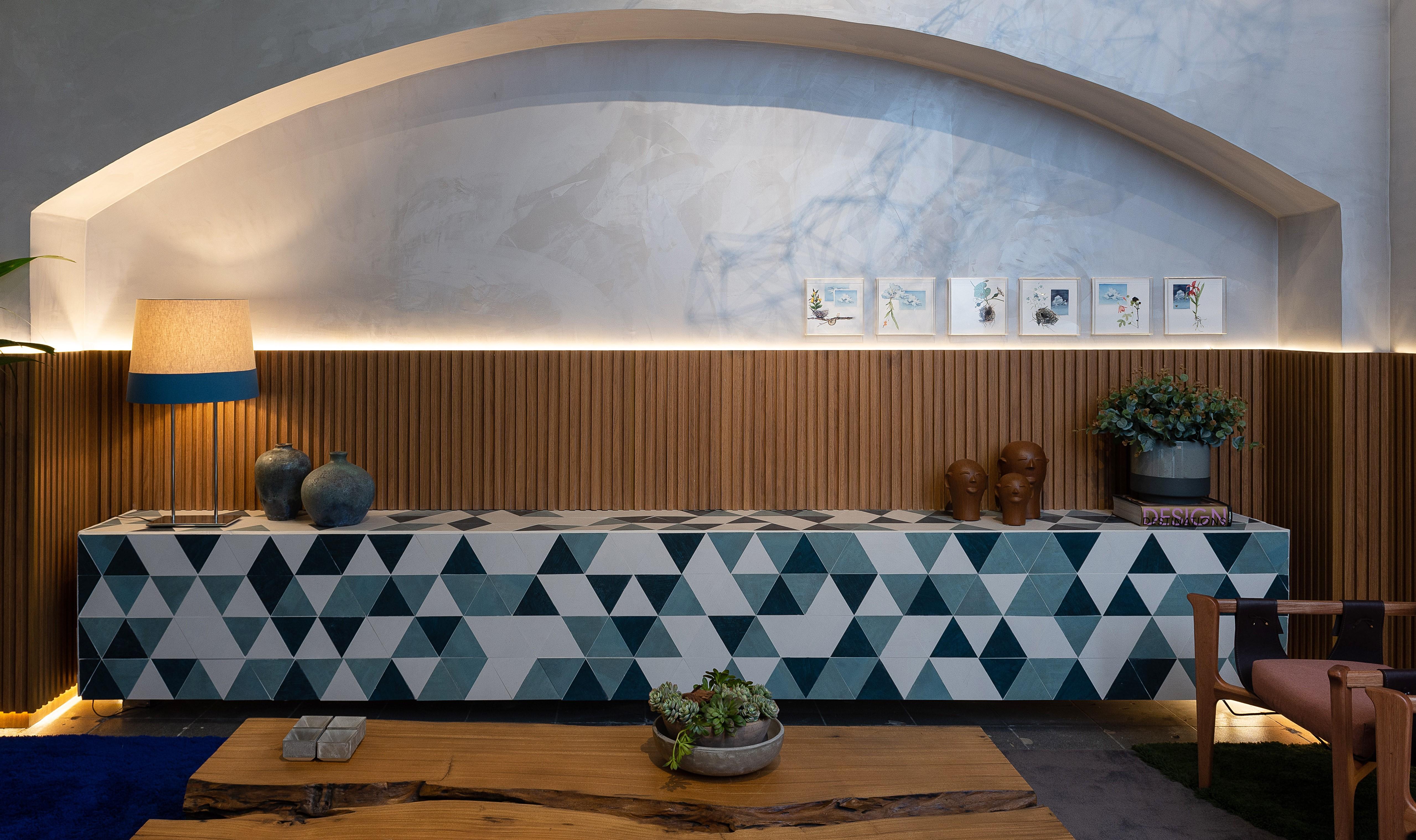 Ambiente com mesa de madeira bruta, poltrona de madeira e um enorme balcão com figuras geométricas. Nas paredes, porcelanato que imita mármore e madeira.   Weiss Arquitetura na CASACOR 2019.