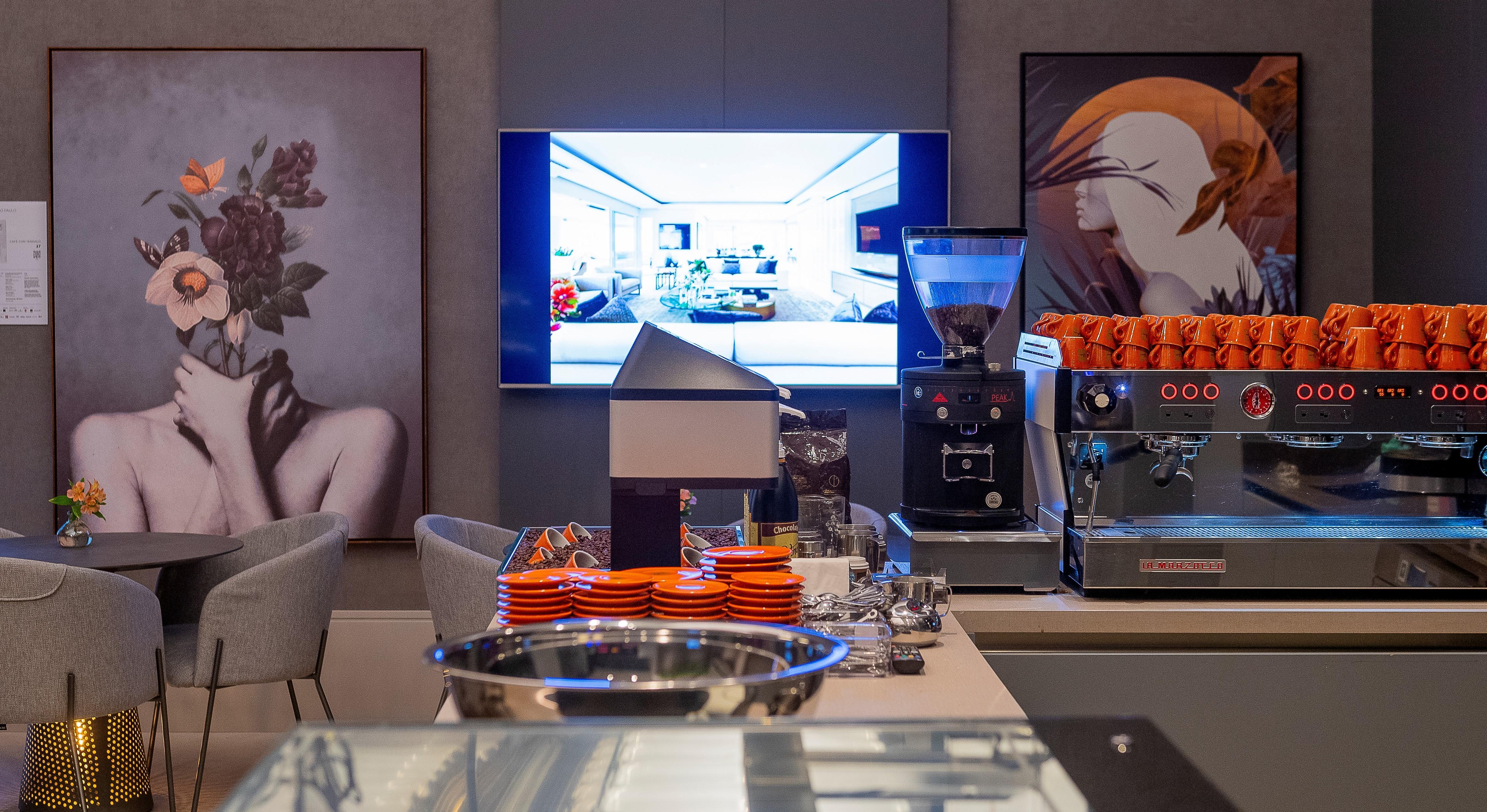 Espaço da ofner na CASACOR SP 2019. Jóia Bergamo. Bancada em laminado Linho, Cafeteiras, pequenas xícaras e pires laranjas, quadros conceituais na parede e um monitor suspenso.