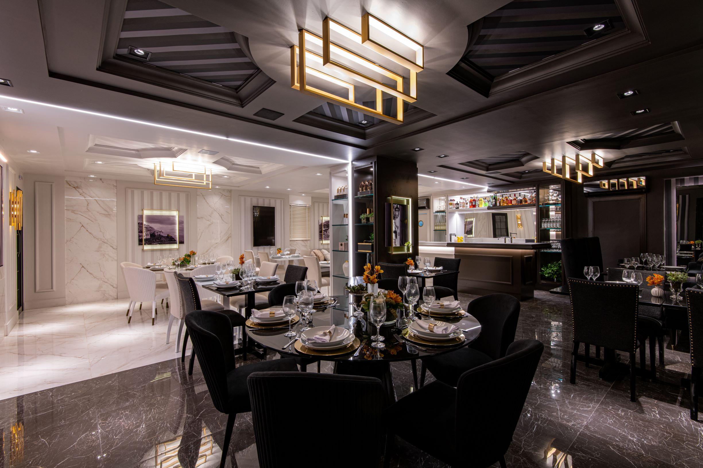 """Restaurante Limone, CASACOR São Paulo 2019, Habitat Projetos Inteligentes. """"Lado noite"""", porcelanato que imita mármore, cadeiras clássicas pretas, mesas de mármore preto, armários marrons e teto com revestimento de gesso e relevo."""