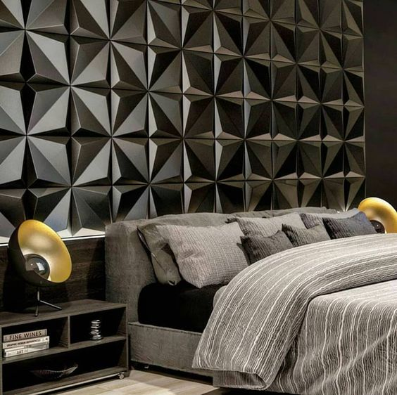 53 ambientes com revestimentos 3D para te inspirar Quarto com decoração urbana em tons preto e cinza. Cama espaçosa com roupa de cama cinza, criado mudo de madeira, abajures modernos, cabeceira de revestimento 3D preta com formas geométricas e piso com revestimento claro.