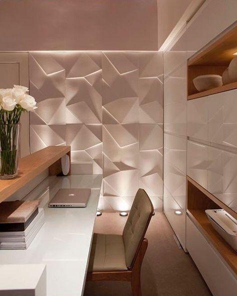 53 ambientes com revestimentos 3D para te inspirar Home Office com mesa e armários brancos e detalhes em madeira, poltrona com pernas de madeira, parede com revestimento 3D e luzes no chão.