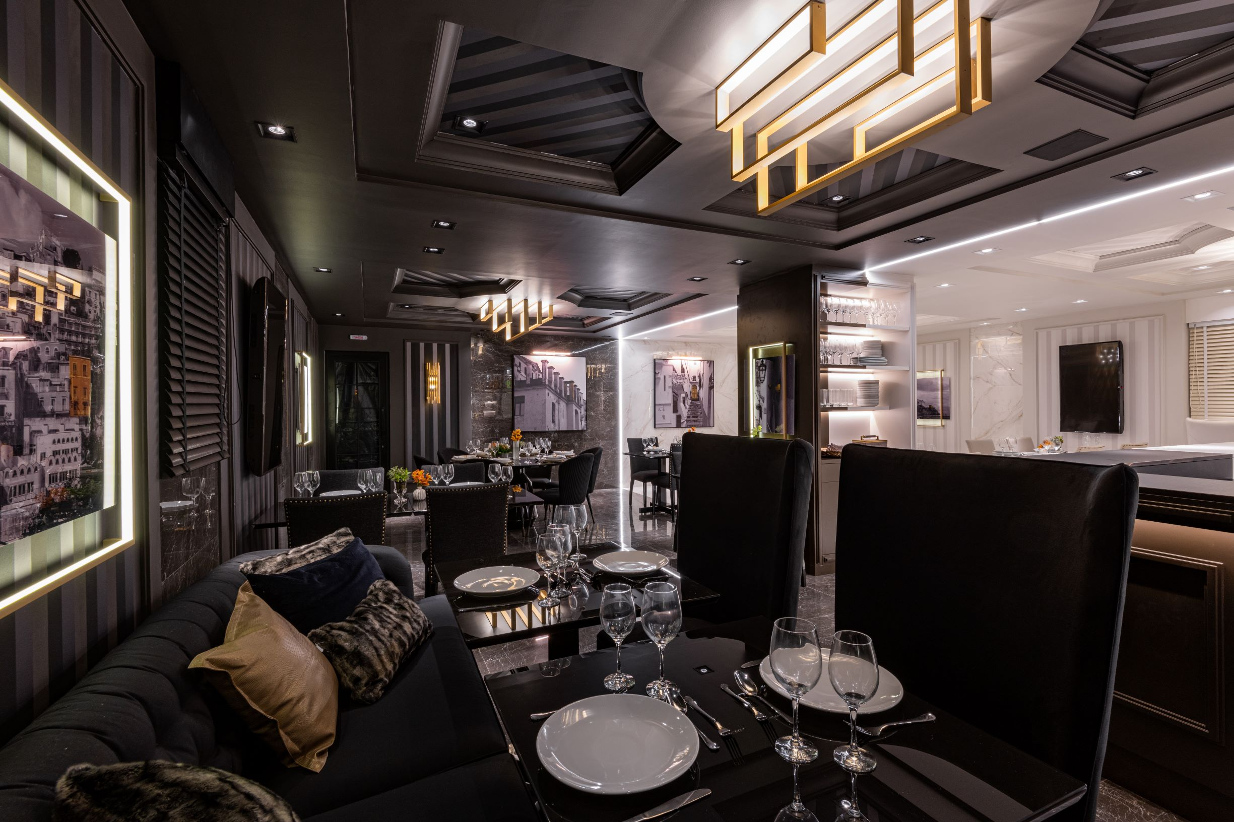 """Restaurante Limone, CASACOR São Paulo 2019, Habitat Projetos Inteligentes. restaurante com conceito de dualidade. """"lado noite"""", teto de gesso com relevo, cadeiras clássicas pretas, sofá preto clássico, mesa de mármore preto e utensílios."""