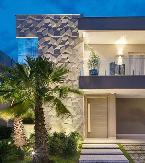 53 ambientes com revestimentos 3D para te inspirar Fachada de imóvel de luxo com dois andares, revestimento geométrico 3D, uma extensa varanda no segundo andar e no quintal existem dois coqueiros.
