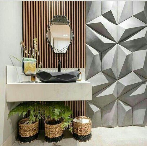 53 ambientes com revestimentos 3D para te inspirar Banheiro. Pia de mármore, cuba com revestimento 3D, parede com revestimento de madeira ripado, espelho triangular e parede com revestimento 3D em formas geométricas.