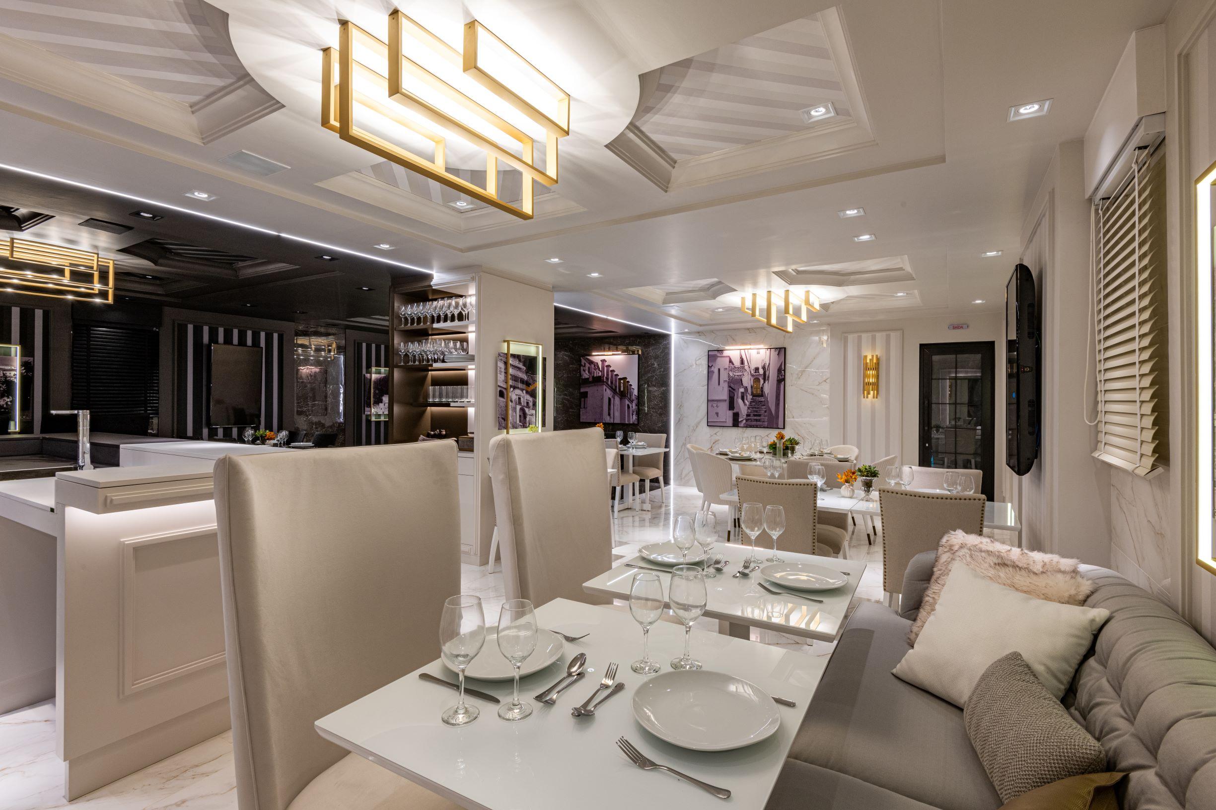 """Restaurante com conceito de dualidade. """"Lado dia"""", cadeiras clássicas brancas, mesa de mármore branco, sofá cinza claro, persianas e teto de gesso com relevo."""