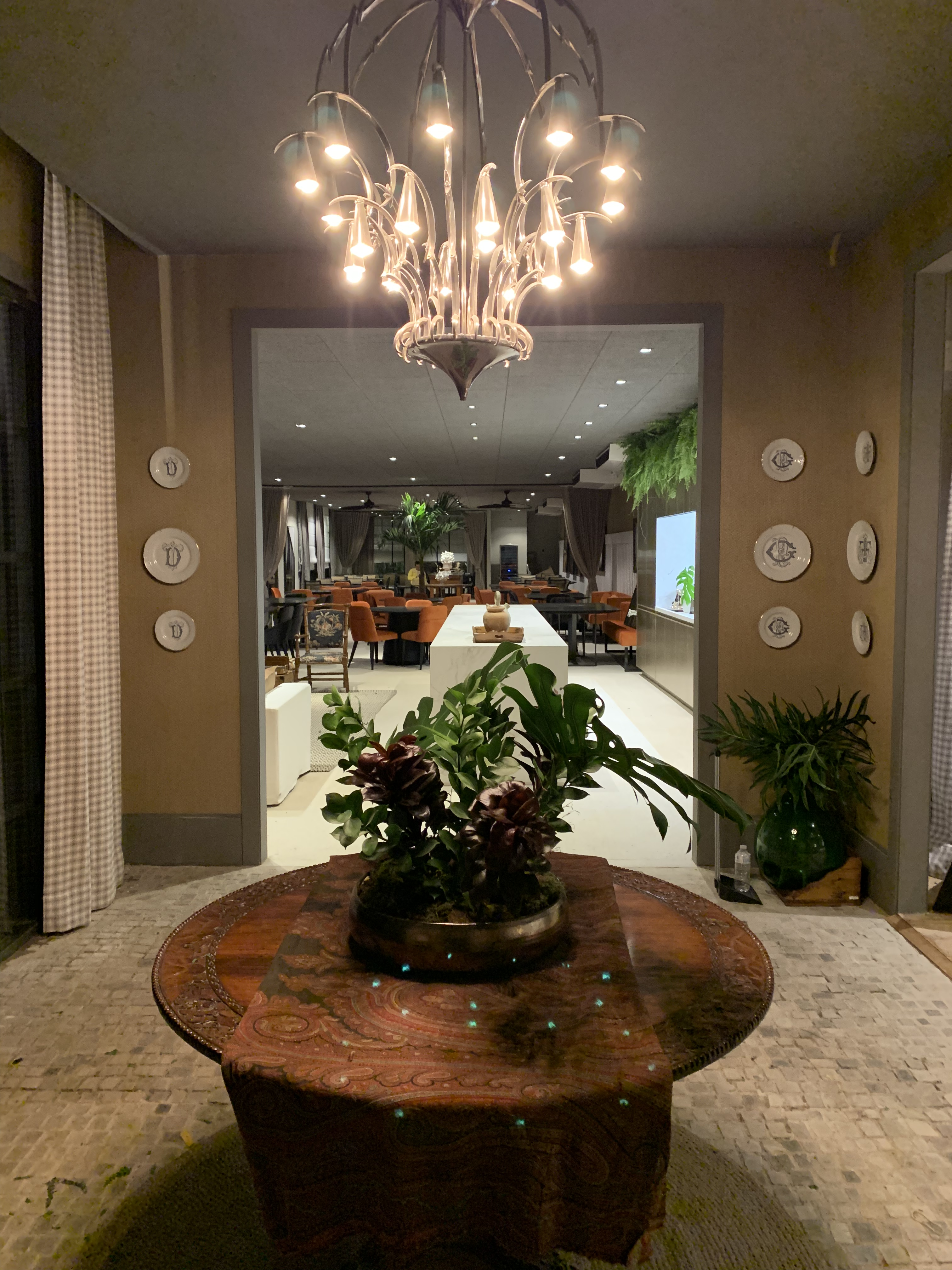 Hall revestido com a coleção Battuto, no piso. Grande mesa de madeira, sofisticado lustre e ao fundo o lounge do restaurante.