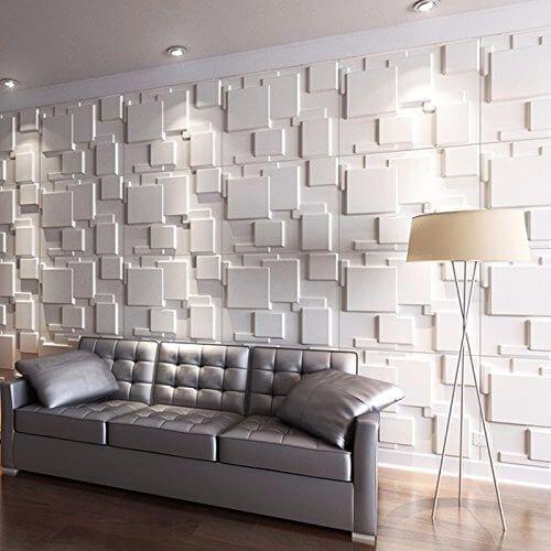 53 ambientes com revestimentos 3D para te inspirar Ambiente clean. Sala de estar com: sofá com cor metálica, Abajur, piso de porcelanato que imita madeira e parede revestida com material 3D em formas geométricas.