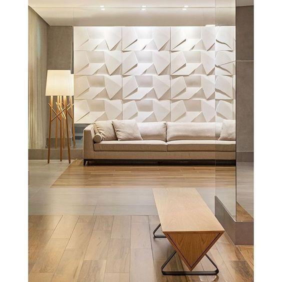 53 ambientes com revestimentos 3D para te inspirar Sala de estar clássica com design limpo. Piso revestido com porcelanato com efeito madeira, banco e abajur de madeira, sofá branco e painel com revestimento 3D Scaleno