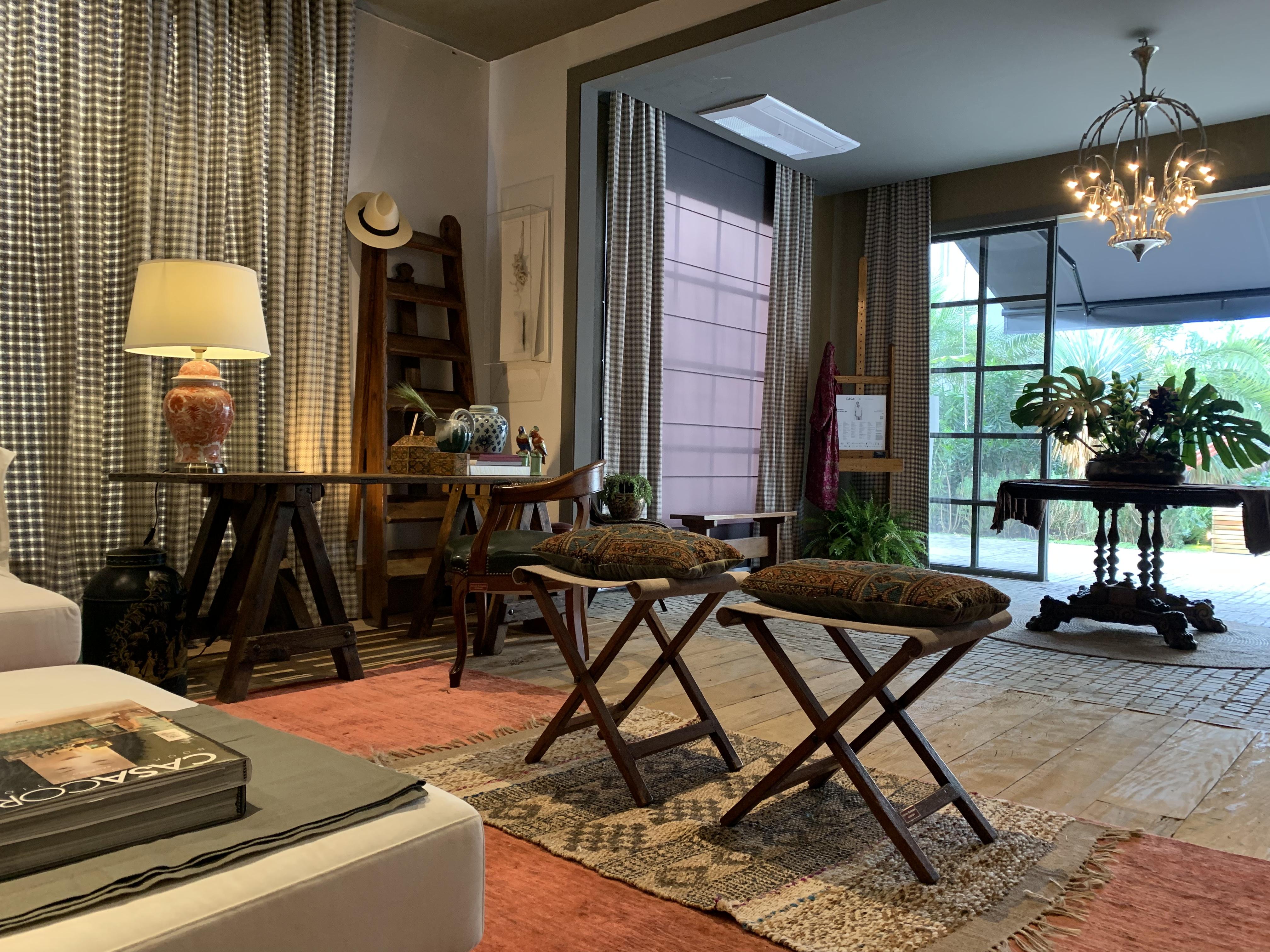 Fotografia do living e hall com visão para área externa. Em primeiro plano estão bancos de madeira retrateis e tapete étnico. Em segundo plano, lustre e mesa do hall. E ao fundo, a porta de vidro.