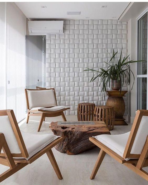 53 ambientes com revestimentos 3D para te inspirar Varanda elegante com um toque rustico. Mesinha de madeira natural bruta, poltronas de madeira com estofado branco, piso de cor clara e parede com revestimento 3D discreto.