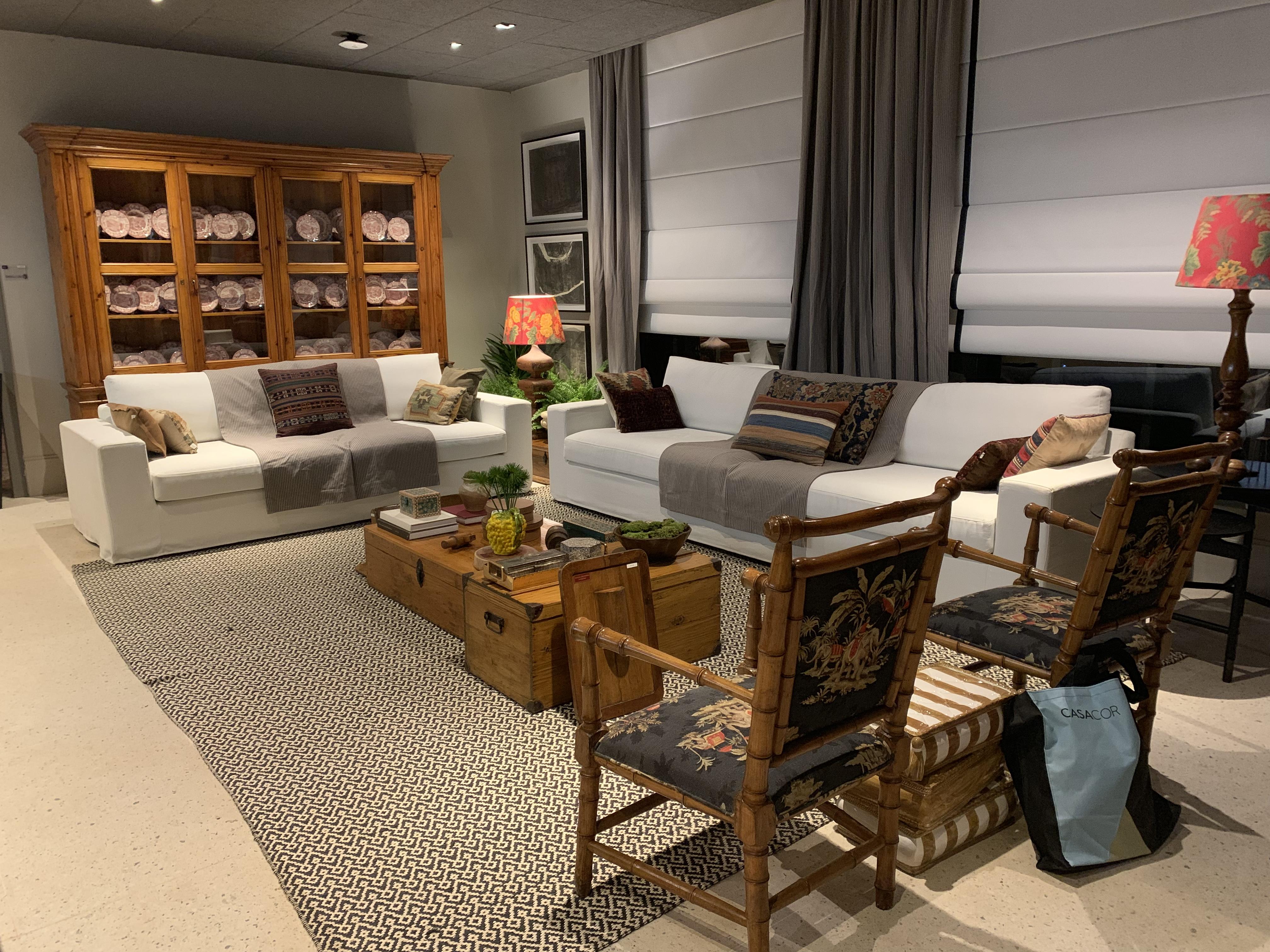 Área do bar com as cores preto e branco, como predominantes, sofá branco, duas poltronas pretas, baus de madeira, persinas brancas, tapete étnico e armário de madeira antigo.
