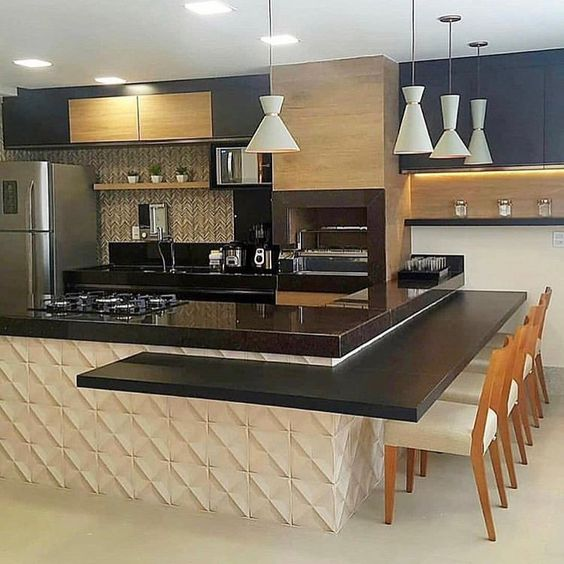 53 ambientes com revestimentos 3D para te inspirar cozinha com tons bege, preto e inox.  Balcão de cozinha americana com parede revestida de material 3D e mesa de granito, armário de madeira, pia de granito e geladeira de inox.