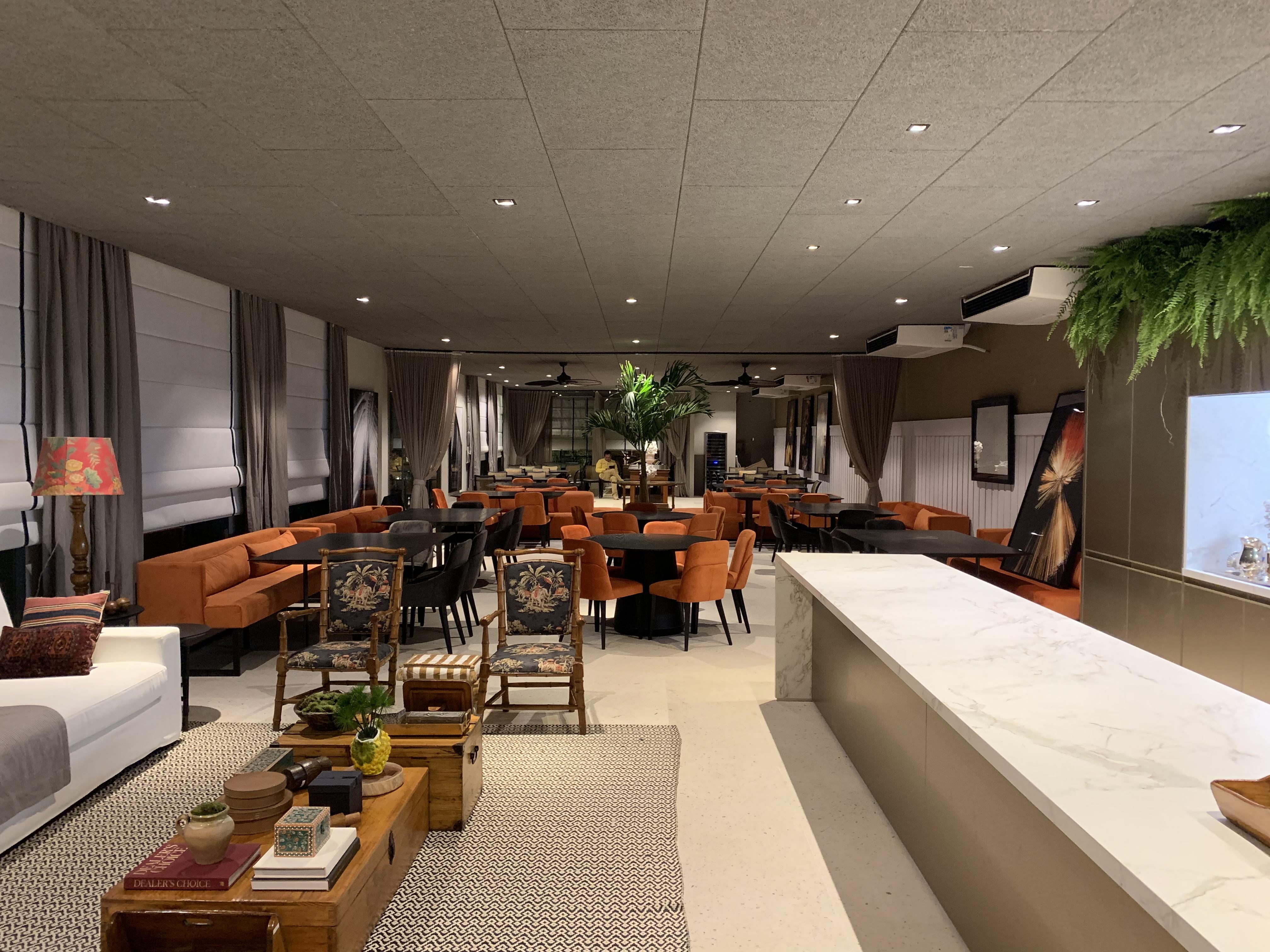 Lounge sofisticado ao fundo com cadeiras e sofás em sarja e duas salas privativas. E bar com ilha e móveis garimpados.