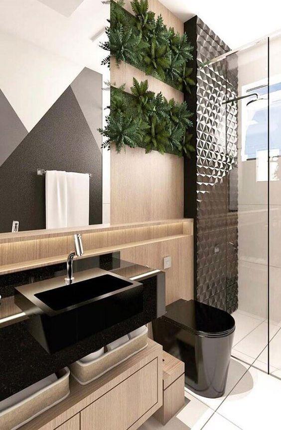 53 ambientes com revestimentos 3D para te inspirar Banheiro; pia de granito, gabinete de madeira, painel de madeira, cuba preta e sanitário preto moderno, box com vidro e parede revestida com material 3D preto com formas geométricas.