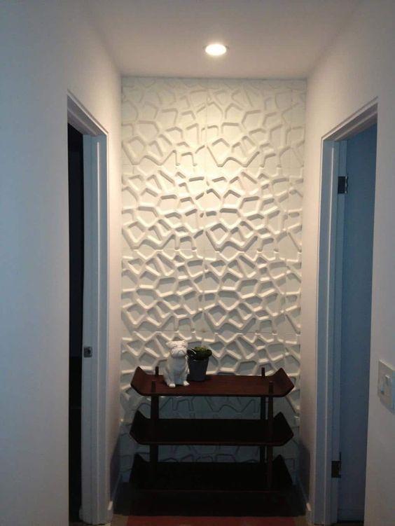 53 ambientes com revestimentos 3D para te inspirar Corredor com parede revestida em material 3D e uma mesinha de madeira no estilo japonês.