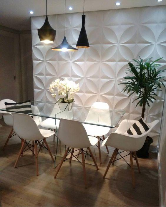 53 ambientes com revestimentos 3D para te inspirar Parede com revestimento 3D. Sala de jantar com revestimento branco 3D na parede, e porcelanato que imita madeira no piso. Mesa de vidro, cadeiras brancas com pés de madeira e luminárias pretas de diversos formatos.