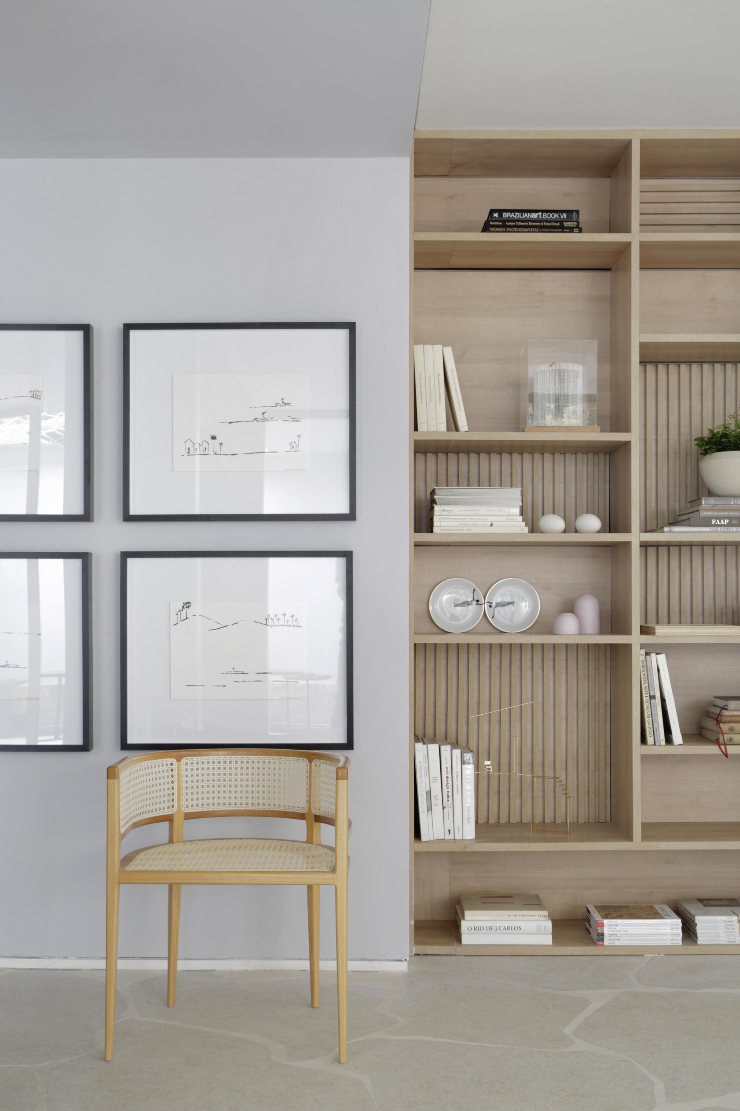 Casa Conecta: Ticiane Lima, CASACOR SP 2019. uma enorme estante nichada que cobre a parede inteira, e exibe a tonalidade natural da madeira clara, piso em formato de rocha, quadros na parede e uma cadeira clássica de madeira em tom claro.