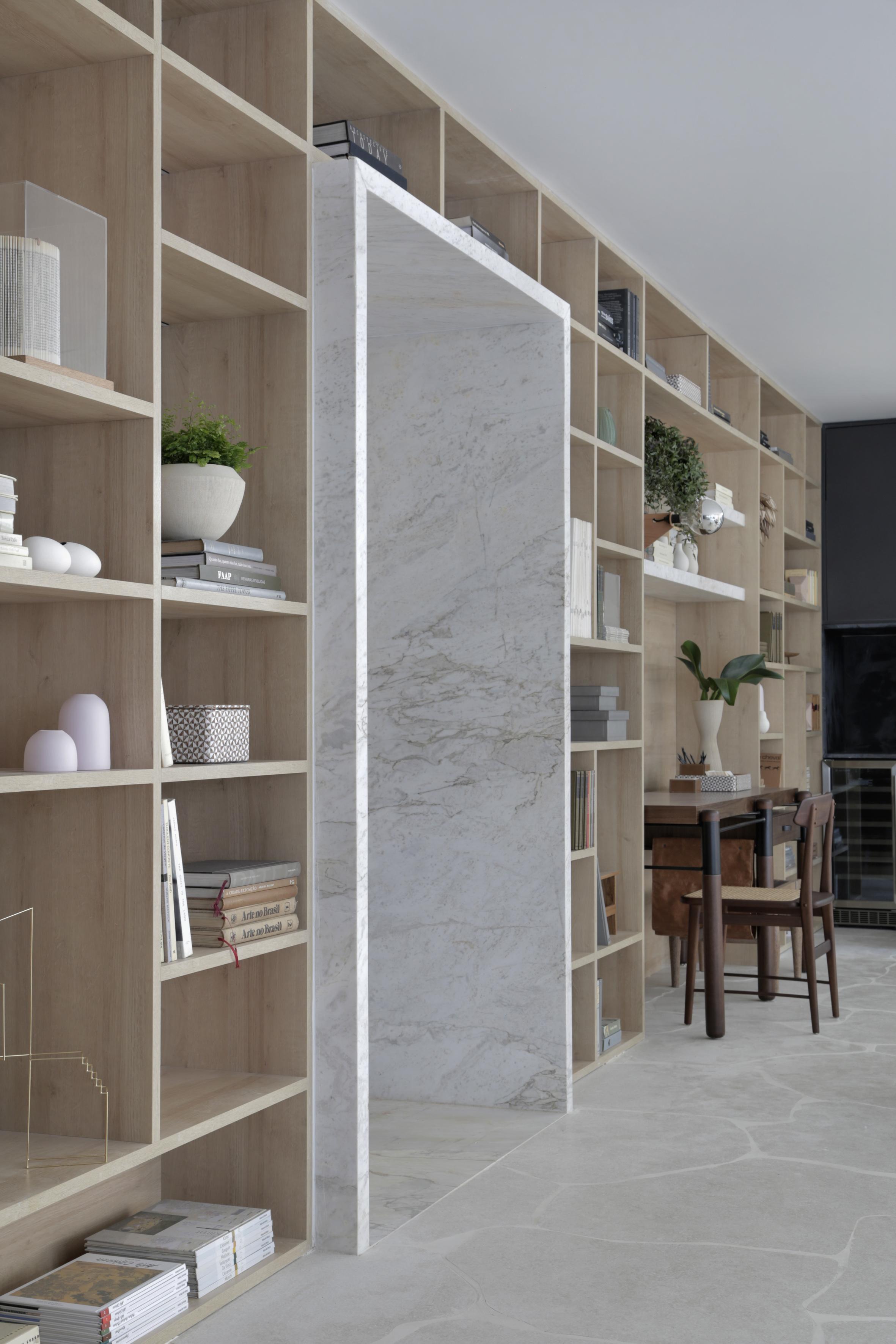 Casa Conecta: Ticiane Lima, CASACOR SP 2019.  Uma enorme estante nichada que cobre a parede inteira, e exibe a tonalidade natural da madeira clara, piso em formato de rocha, entrada com revestimento de mármore e lareira.