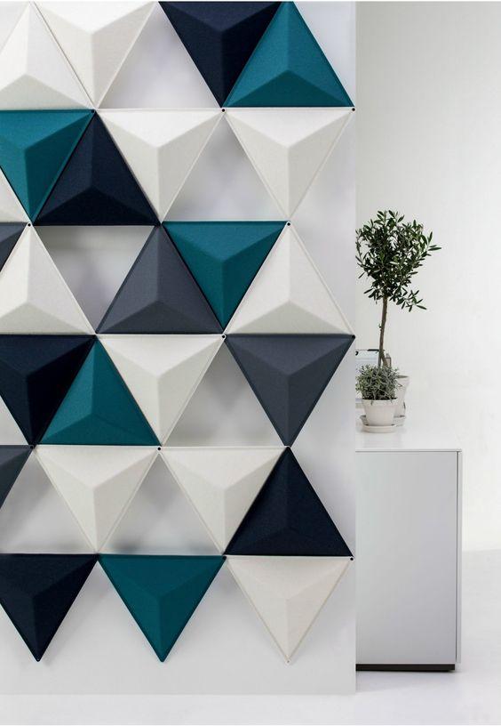 Parede com revestimento 3D. Parede com revestimento 3D no estilo padronagem irregular, nas cores azul, cinza e branco e formatos triangulares. Ao fundo um armário branco com plantas.