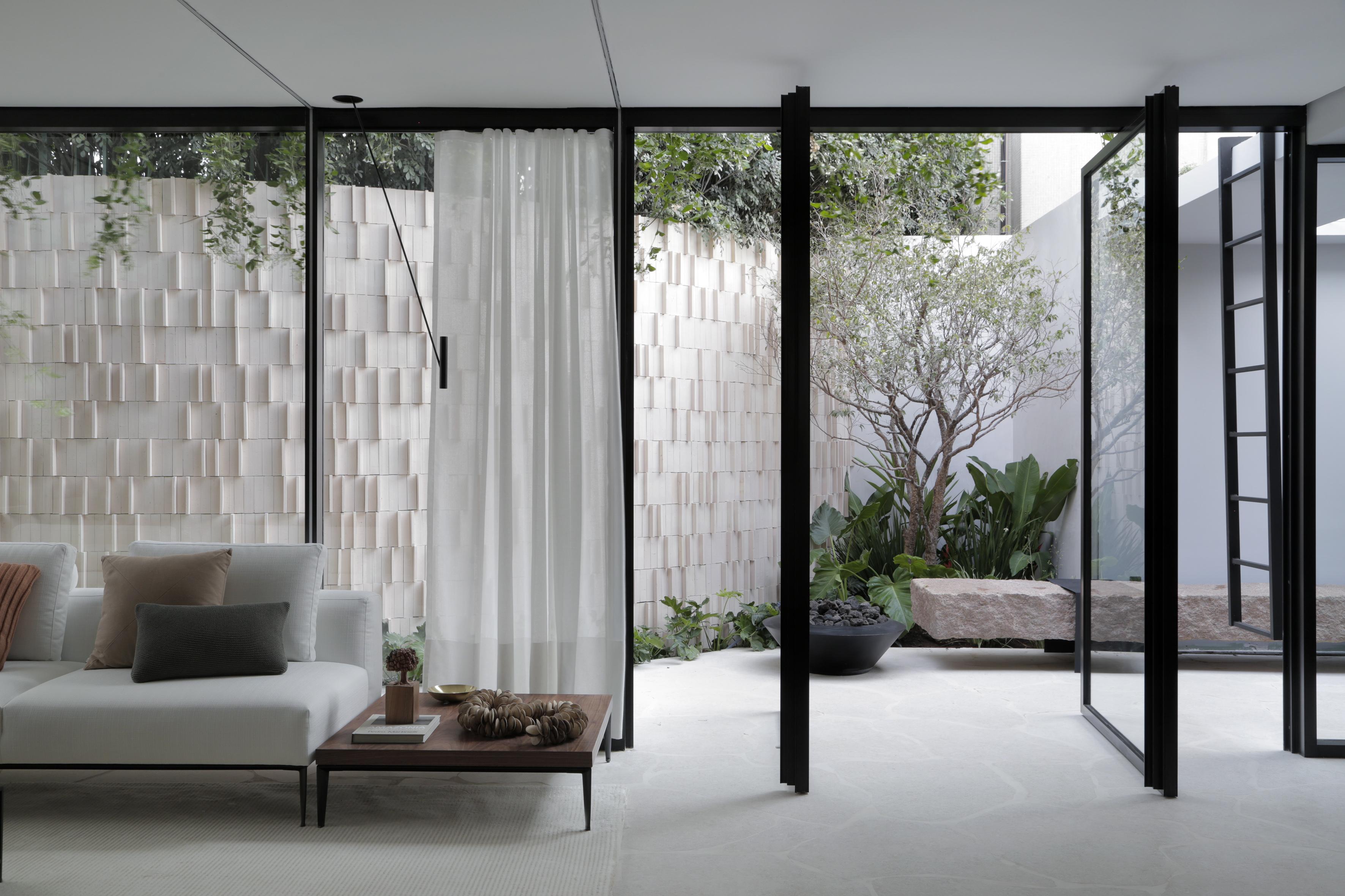 Casa Conecta: Ticiane Lima, CASACOR SP 2019.  jardim e living conectados por panos de vidro. árvore, vasos,  jasmins, e um muro com acabamento em relevo.