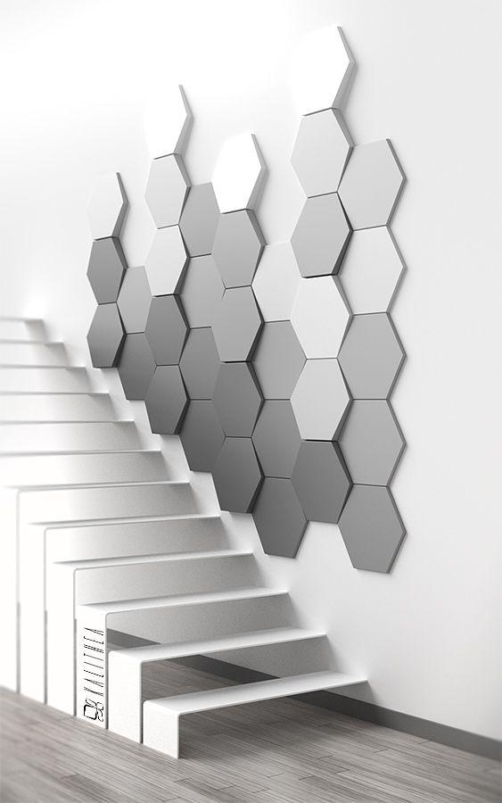 Parede com revestimento 3D. parede de acesso a escada está revestida com material 3D, tem formas hexagonais em degrade com tons de cinza.
