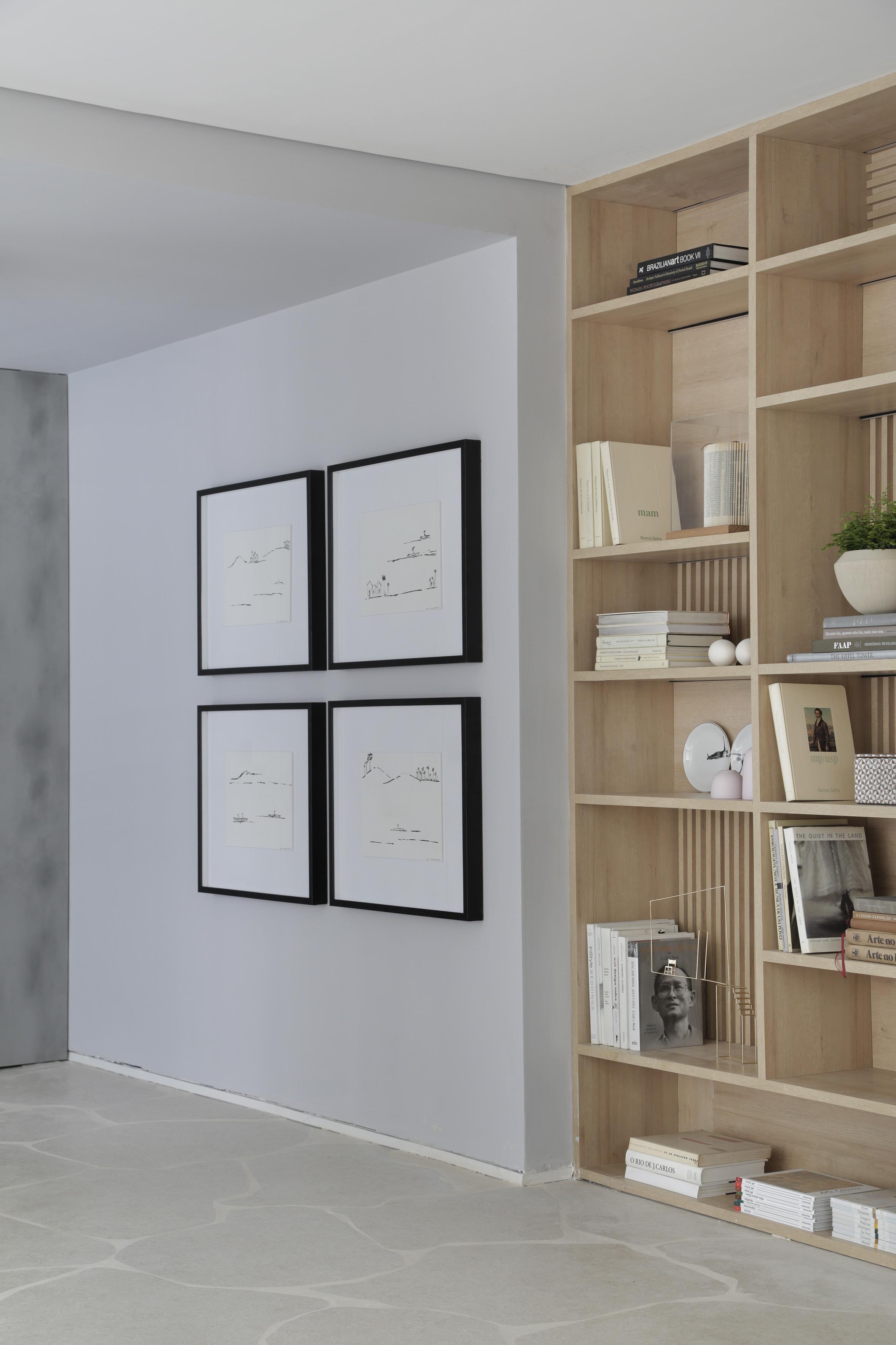 Casa Conecta: Ticiane Lima, CASACOR SP 2019.  Uma enorme estante nichada que cobre a parede inteira, e exibe a tonalidade natural da madeira clara, piso em formato de rochas  e quadros de Zanine e de Maria Kruchewiscky.