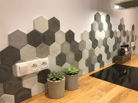 Parede com revestimento 3D. bancada da cozinha de madeira e na parede rente à ela, está os hexágonos em tons de cinza.
