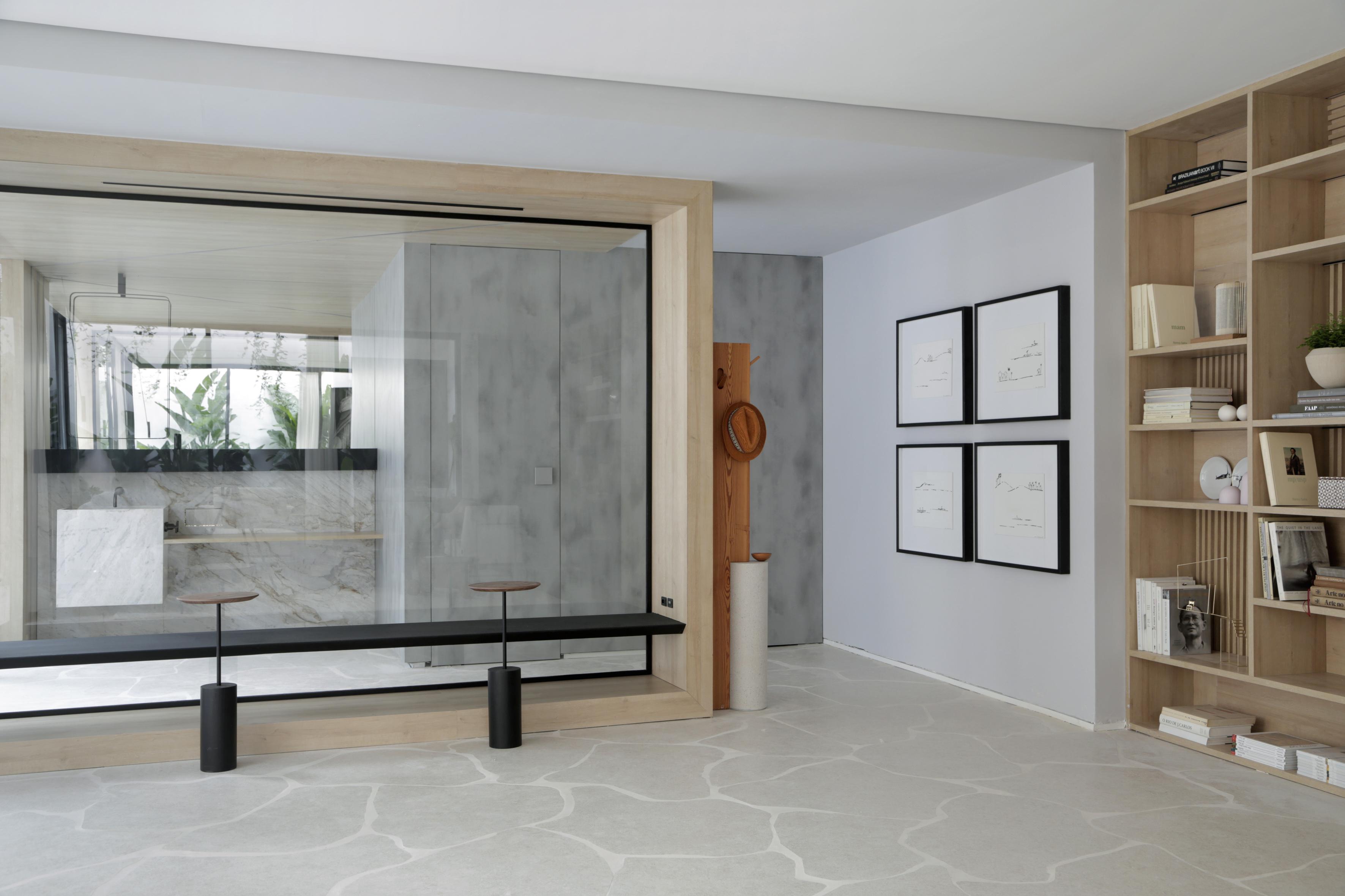 Casa Conecta: Ticiane Lima, CASACOR SP 2019.  Living e banheiros divididos por uma parede de vidro. Uma enorme estante nichada que cobre a parede inteira, e exibe a tonalidade natural da madeira clara, piso em formato de rochas  e quadros de Zanine e de Maria Kruchewiscky.