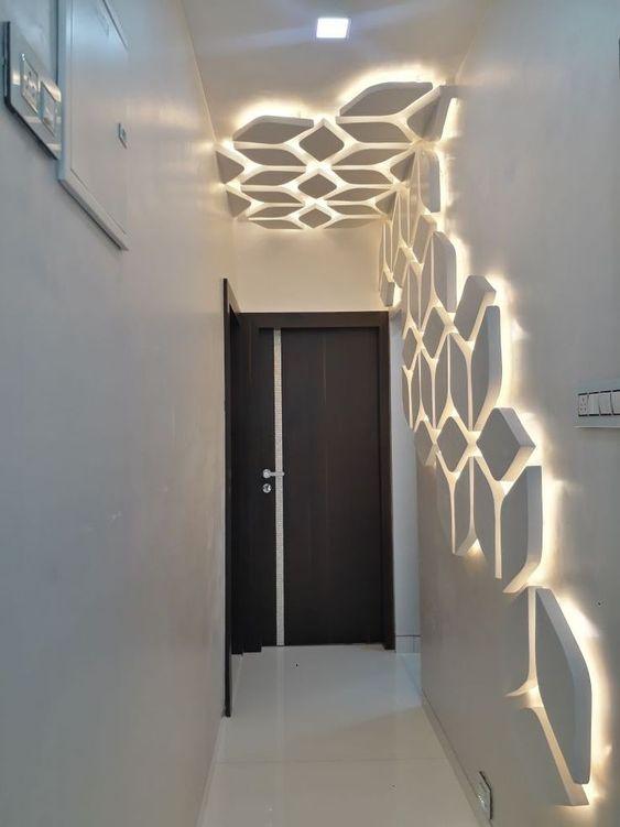 Parede com revestimento 3D. Corredor com paredes brancas. O revestimento, que tem ilusão de cubo, começa na parede e vai até uma área do teto e tem luzes incorporadas.