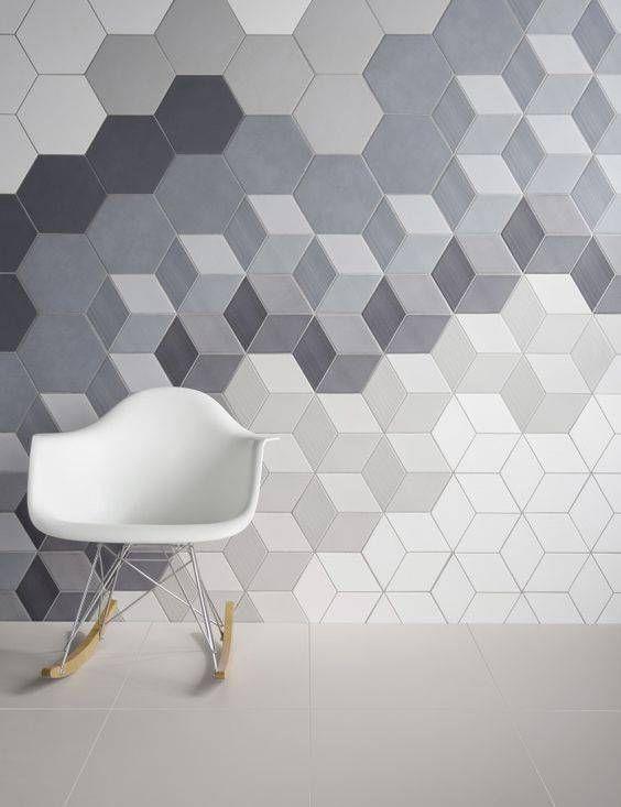 Parede com revestimento 3D. parede com padronagem que mescla o efeito cubo com figuras hexagonal. cadeira branca de balanço e piso de porcelanato claro.