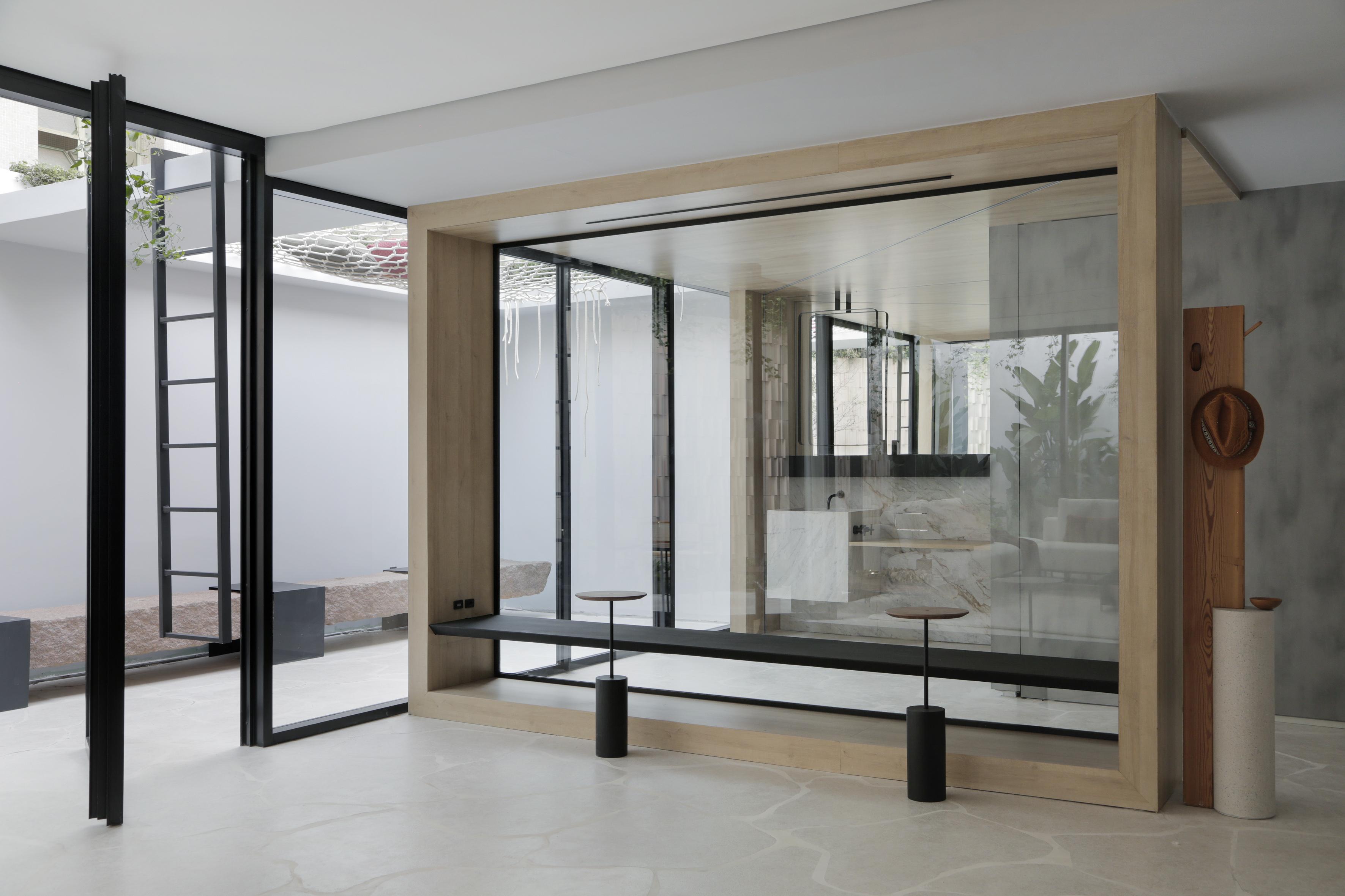 Casa Conecta: Ticiane Lima, CASACOR SP 2019.  Living e banheiros divididos por uma parede de vidro.  cabideira de chapéus, piso em formato de rochas e panos de vidro que limitam área interna e externa.