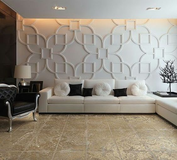 Sala de estar com sofá branco e poltrona preta, revestimento 3D com traços arabescos na parede e piso com traços arabescos.